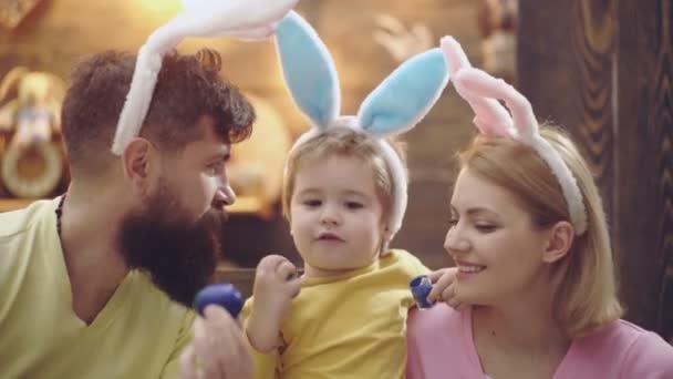 Glückliche Osterfamilie mit Hasenohren. Mutter, Vater und Sohn bemalen und verzieren Eier für den Urlaub. Lustige Gesichter.