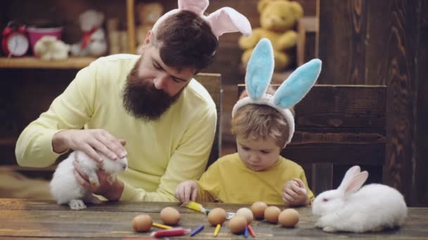 Family play with easter bunny rabbit. Father and son with easter bunny ears.