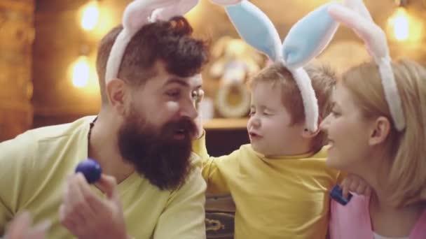 Frohe Osterfamilie beim Bemalen von Eiern. Mutter, Vater und Sohn tragen Hasenohren. Lustige Gesichter.