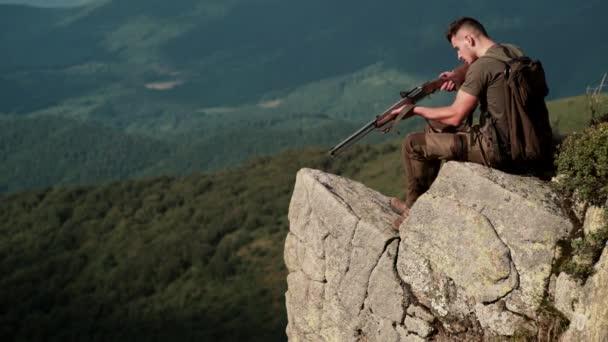 Vadász. Vadászati időszak, őszi szezon. Egy fegyveres fickó. Egy vadász vadászpuskával és vadászattal egy őszi erdőben..