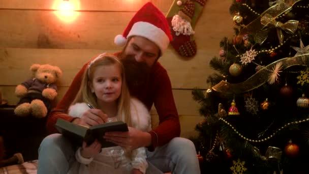 Lächelnd schreiben Vater und Tochter einen Weihnachtswunsch an den Weihnachtsmann. Familienweihnacht, Kinderglück und Menschen-Konzept.