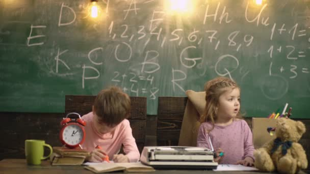 Pupils in elementary school. Kids in classroom. Boy and girl sitting at desk and writing a text. Cute children drawing, preschool child study. Education, homeschooling preschool concept.
