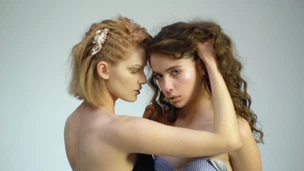 Krásné dívky se zlatým make-up dotknout navzájem na bílém pozadí. Erotický koncept. Módní zlatý model ukazuje luxusní koncept. Péče o vlasy a pleť.