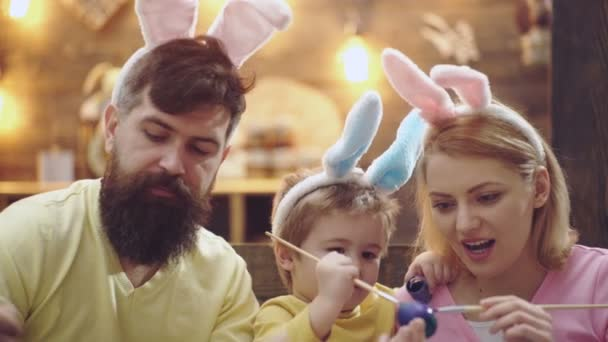 Happy easter family. Mother, father and son wearing bunny ears and painting eggs. Funny faces close up.