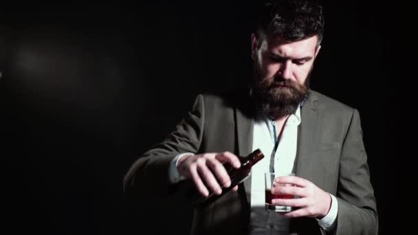 Pohledný muž se sklenicí moudrosti. Veselý vousatý muž pije drahou whisky brandy nebo koňak.