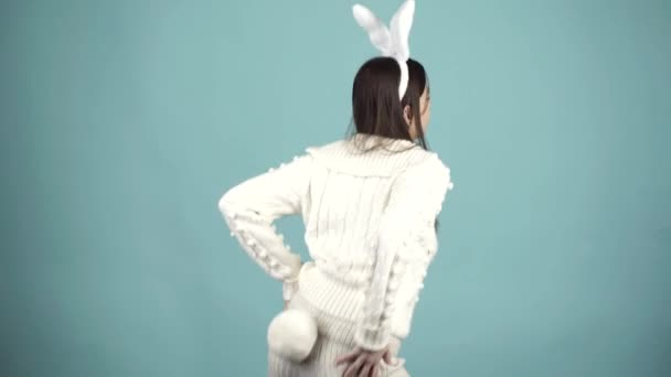 Funny model dressed in costume Easter bunny, standing on a blue background and sensually posing. Portrait of happy Easter bunny woman. Crazy girl celebrating easter.