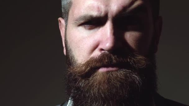 Emoce mužské tváře. Detailní portrét seriózního brutálního vousatého muže na tmavém pozadí. Sebevědomé a dramatické.