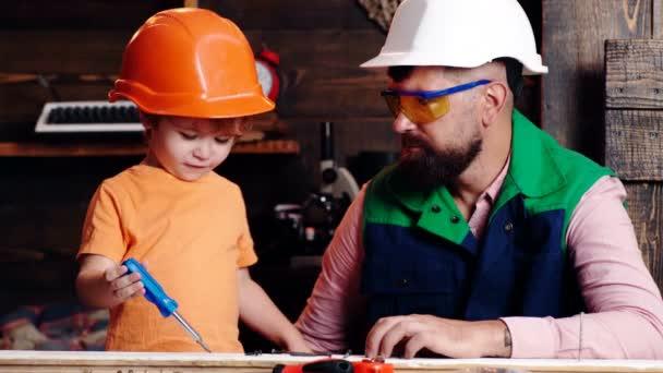Apa és fia együtt dolgoznak. A gyerekek tanulási eszközei apával. Szülő a védő sisak tanítás kisfia, hogy használja a különböző eszközök az iskolai műhelyben.