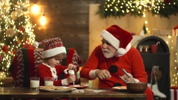 Stilvolle bärtige Weihnachtsmänner backen weihnachtliche Ingwerplätzchen zu Weihnachten. Weihnachtsmann-Helfer bereiten Weihnachten oder Neujahr vor.