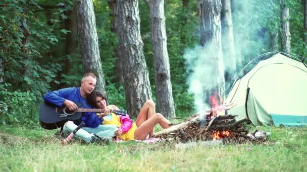 Pár letních pikniků. Společnost se utábořila v lese. Muž a žena zpívají s kytarovým ohněm.