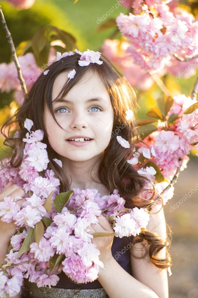 Little girl amid cherry blooming