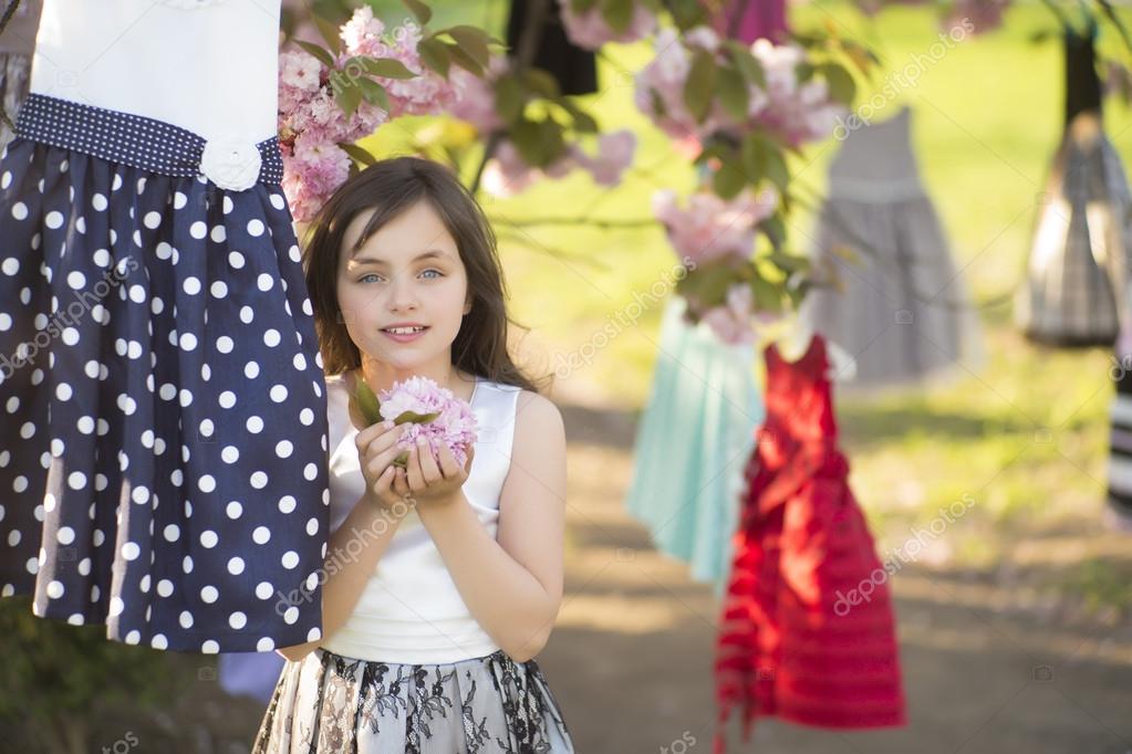 Little girl among dresses in the tree