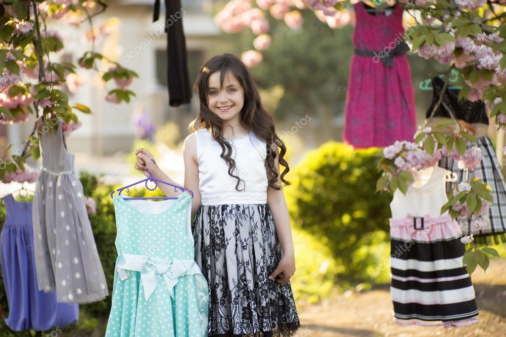Little girl choosing dresses