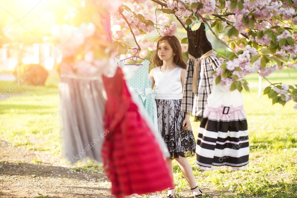 Cute girl among dresses in the tree