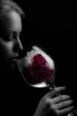 woman smelling a flower in a glass