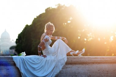 Attractive bride sitting on bridge