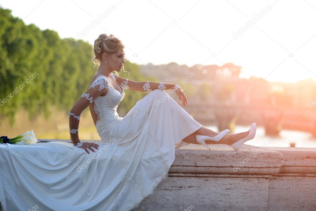 Beautiful bride sitting on bridge