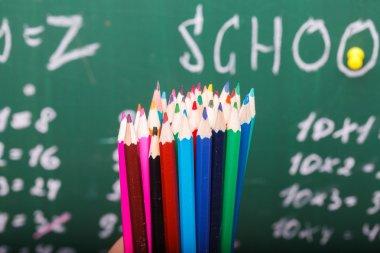 Colorful pencils and school blackboard