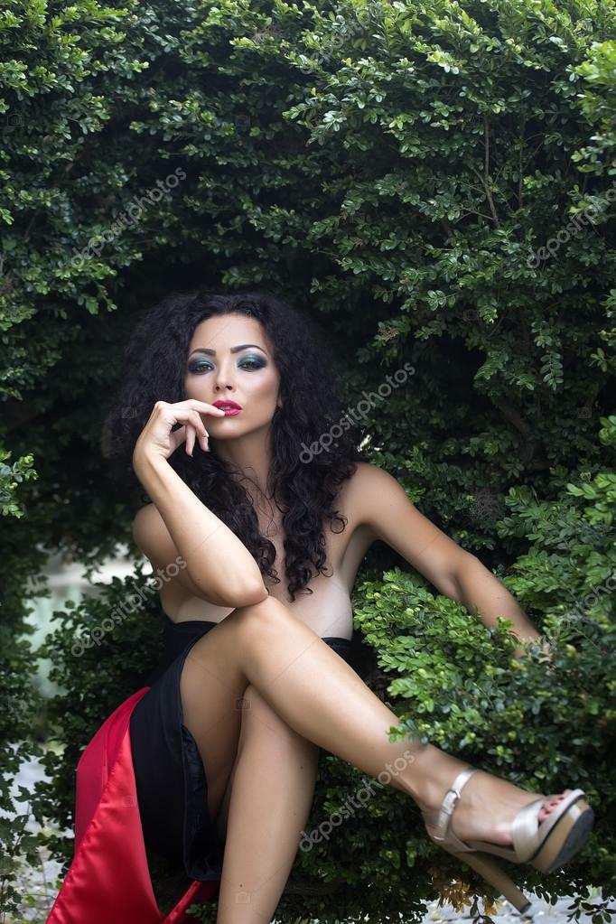 Sweet Sensual Young Woman With Curly Long Hair With Bright Make Up In Sexy Dress With Bare Shoulders Looking Straight Posing With Her Beautiful Legs Crossed
