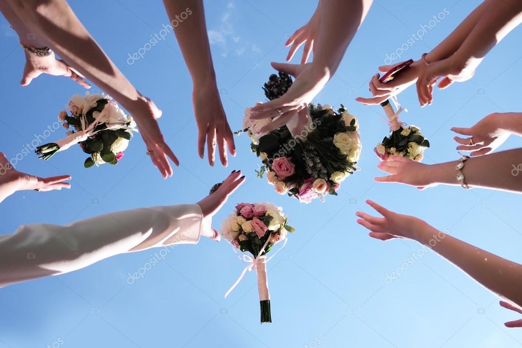 Hands catch bouquets