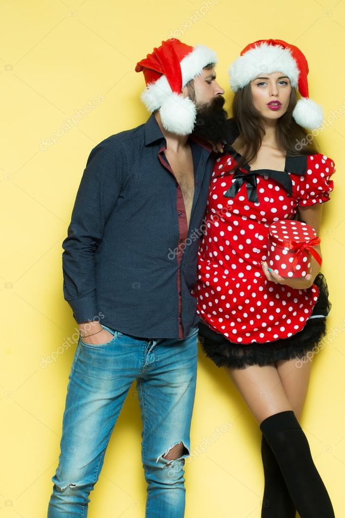 Beautiful Cute Young Funny Couple Of New Year Man With Long Black Beard And Woman In Red Dress Santa Hat Holding Gift Box For Christmas Standing
