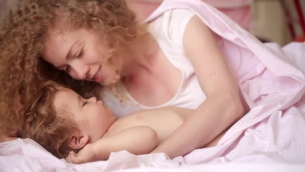 Beautiful young mother tenderly kissing the sleeping baby