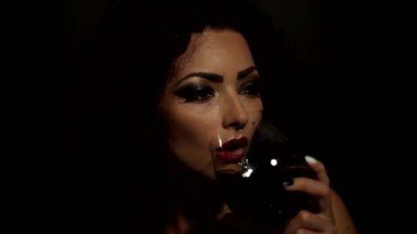 krásná dívka pití z sklenku červeného vína, izolované na černém pozadí