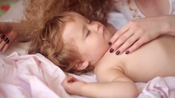 mladá krásná kudrnatá dívka s láskou pohledu na dítě a hladila jeho drzost, když on sladce spí