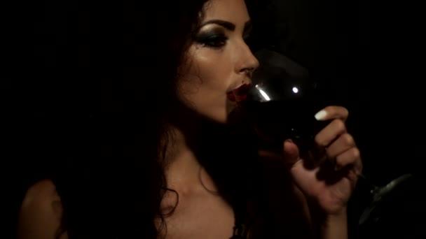 mladá atraktivní žena odvrátila a ochutnávka červené víno s sklenice na víno