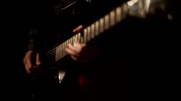 Este a gitár, egy tehetséges zenész játszik a gitár húrok, a fekete háttér