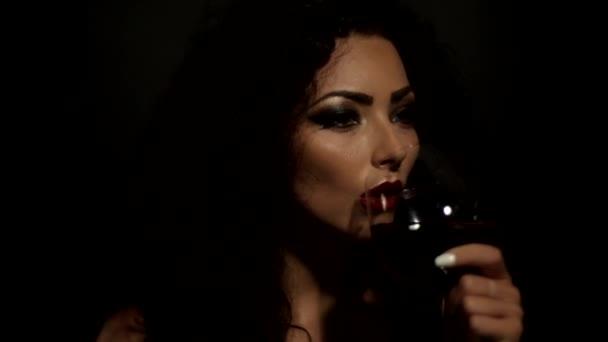 krásná mladá dívka pije víno s brýlemi a vypadá to, že hraje víno ve sklenici proti světlu