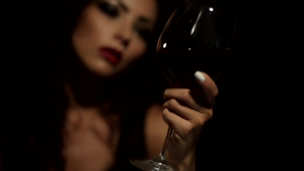 beautiful girl looks at a glass of wine and with relish tasting drink