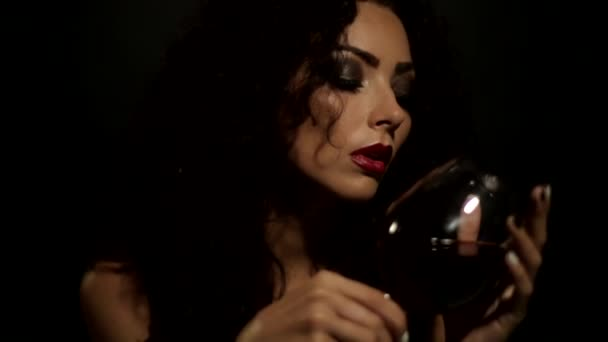 sexy girl dips a finger in the wine and licks his