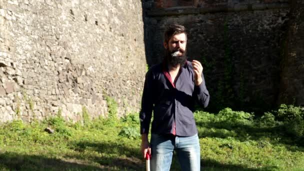 vousatý muž kouří a hraje si s sekeru na pozadí středověkých hradeb