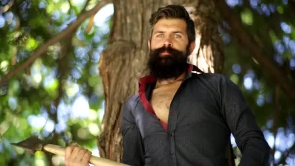 pohledný muž s modrými zraky v lese hází sekyru na rameno