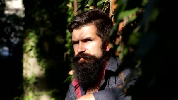atraktivní muž v parku olízl ostří sekyrou