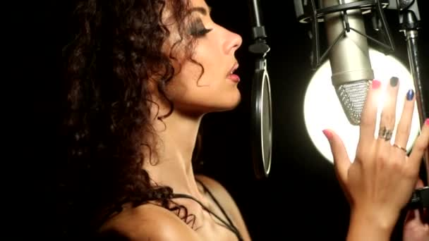 curly girl seductively caresses the microphone in the studio