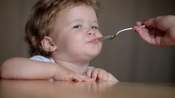 Sladké dítě krmení lžící stolu, chlapec jíst pevnou stravu