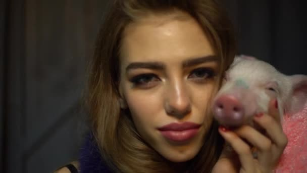 4K beautiful girl and little piggy posing together on camera