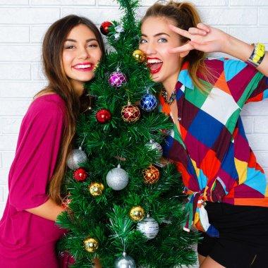 women posing near Christmas tree