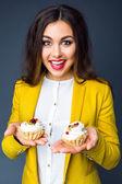 Frau hält zwei leckere Kuchen in der Hand