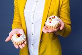 Nahaufnahme Porträt einer Frau mit zwei Kuchen