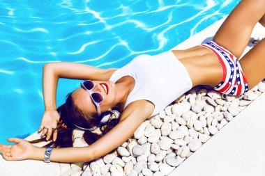 young sexy dj girl laying near pool