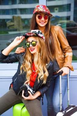 Young pretty sisters sitting on baggage, having fun together, end ready for new adventures travel, wearing bright stylish clothes and sunglasses, positive emotions mood. urban background stock vector