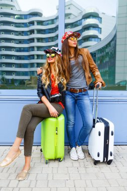 Young friends girls going crazy about their new trip, screaming laughing and having fun near airport with their bright luggage, enjoy travel together. Positive playful emotions, urban background stock vector