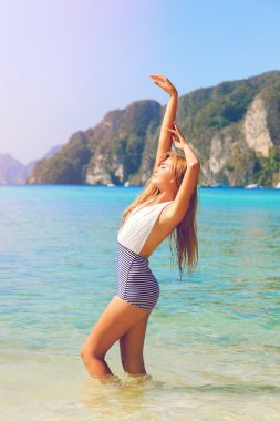 tan woman posing at tropical island