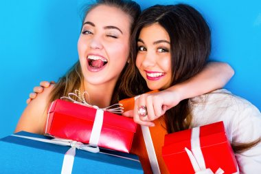 girls holding bright holiday presents