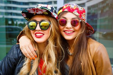 Outdoor lifestyle portrait of couple best friends pretty young girls, hugs and smiling, wearing bright hipster swag outfits and leather jackets, urban background stock vector