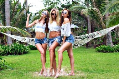 Three women posing at tropical garden