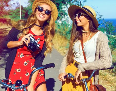 two hipster girls walking with retro bicycles